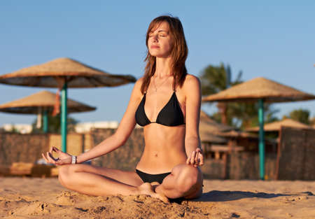 Silhouette of woman in yoga lotus meditation position on the beach Stock Photo - 12249160