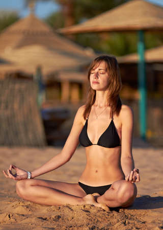 Silhouette of woman in yoga lotus meditation position on the beach photo