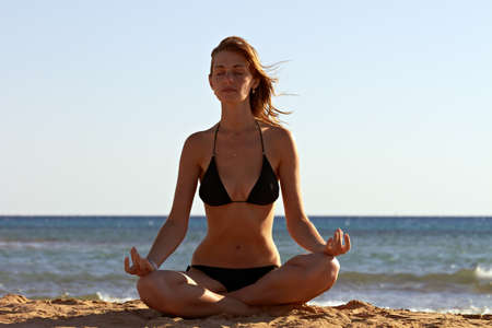 Silhouette of woman in yoga lotus meditation position back to seaside Stock Photo - 12249152