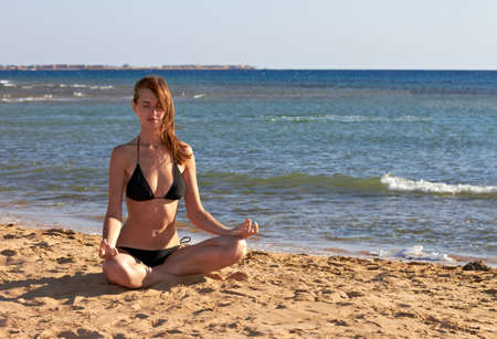 Silhouette of woman in yoga lotus meditation position back to seaside Stock Photo - 12249168