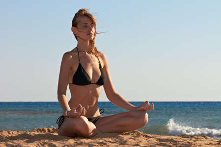 Silhouette of woman in yoga lotus meditation position back to seaside photo