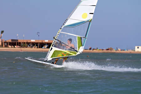 Young man windsurfing with trailing wake photo