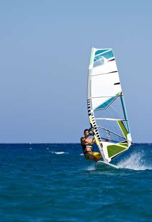 Een jonge man surfen van de wind op een heldere zomerdag