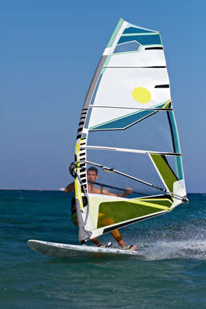 A young man surfing the wind on a bright summer day