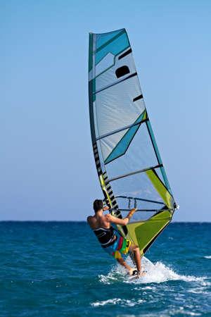 Achteraanzicht van een windsurfer voorbijgangers