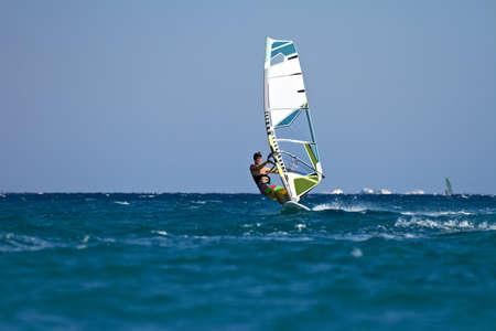 Young male windsurfer in action on sunny day
