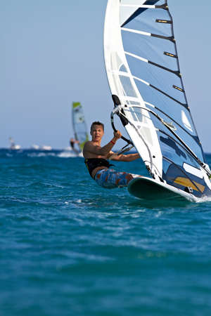 Front view of young windsurfer passing by