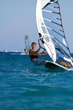 Vooraanzicht van jonge windsurfer passeren door