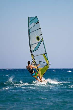 Achteraanzicht van de mens windsurfen in waterspatten