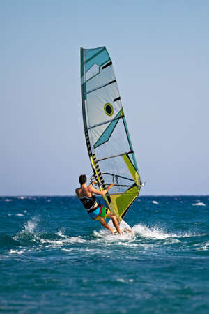 Rear view of man windsurfing in splashes of water Stock Photo