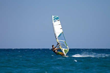 Young male windsurfer in action on sunny day photo
