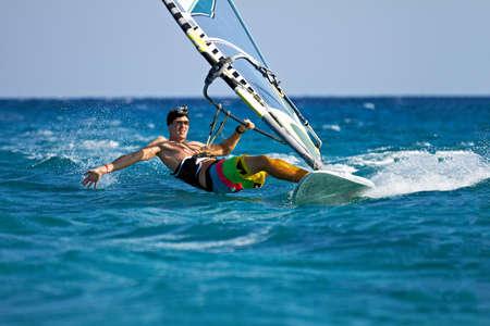 Jeune homme surfer sur le vent et toucher la surface de l'eau avec des touches Banque d'images