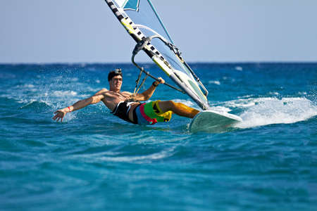 wind surf: Joven navegar por el viento y el contacto con la superficie del agua con salpicaduras