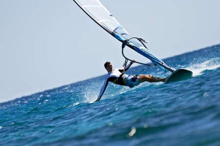 Jongeman surfen van de wind en het aanraken van het water oppervlak met spatten