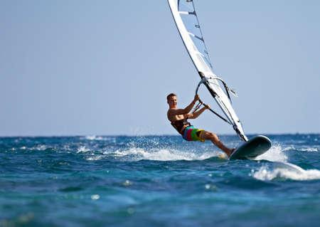 Jongeman surfen van de wind op een heldere zomerdag