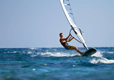 sports: Young man surfing the wind on a bright summer day