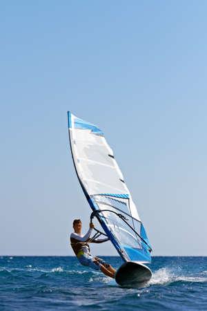 Vooraanzicht van jonge man surfen op het wind op zomerdag