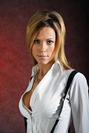 Mooie jonge vrouw in sexy kleding poseren op een donkere achtergrond Stockfoto