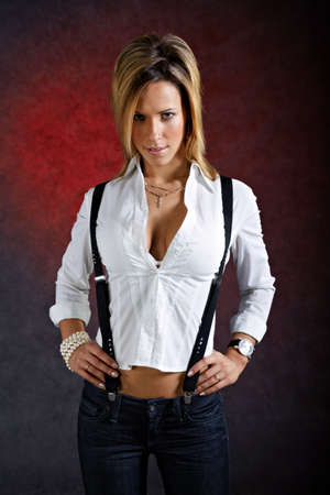 suspenders: Young woman in sexy clothes with suspenders posing on dark background