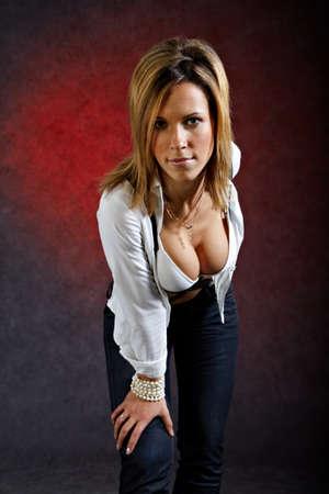 Jonge vrouw in sexy kleding voorovergebogen op donkere achtergrond