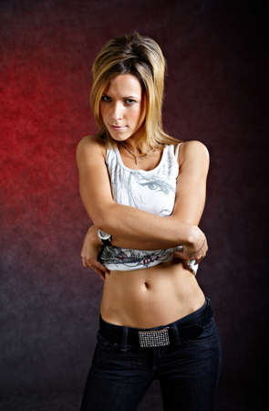 Young woman taking off her clothes sexually on dark background