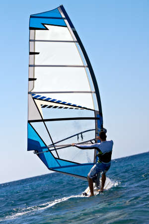 windsurfing: Vista trasera de windsurf hombre de salpicaduras de agua Foto de archivo
