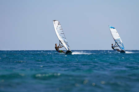 Two windsurfers in action mooving parallel to eath other