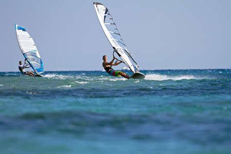 Vooraanzicht van twee windsurfers in actie mooving parallel aan eath andere