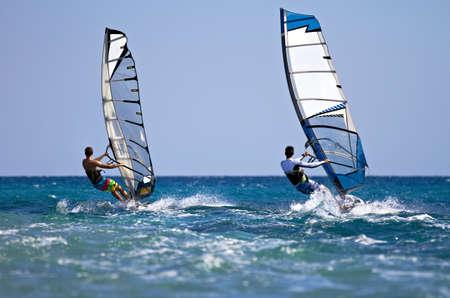 windsurf: Vista trasera de dos tablas de windsurf en la acción mooving paralela a otra eath Foto de archivo