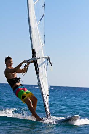 Jongeman surfen de wind op een heldere zomerdag