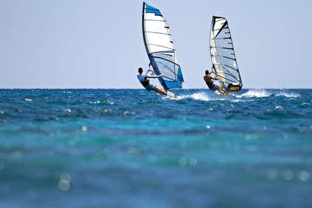 Achteraanzicht van twee windsurfers in actie mooving parallel aan andere eath Stockfoto