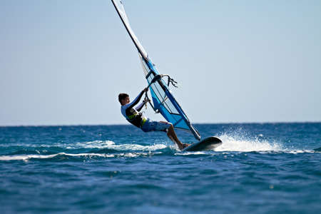 Side view of man windsurfing in splashes of water Stock Photo