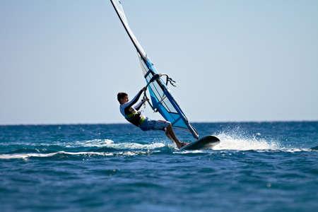 Zijaanzicht van de mens windsurfen in waterspatten