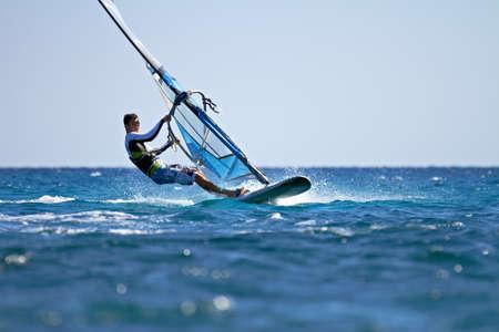 Zijaanzicht van de jonge windsurfer passeren door Stockfoto
