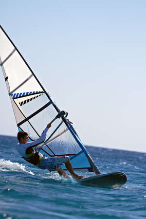 Side view of a windsurfer mooving horizontally close to water surface photo