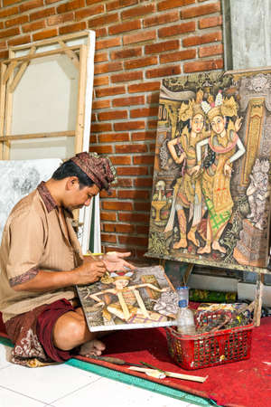 Painter drawing on canvas in gallery, Bali, Indonesia photo