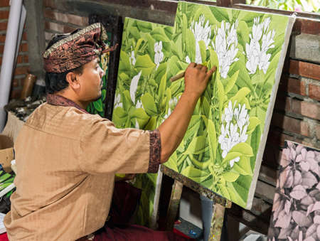 Painter drawing on easel in gallery, Bali, Indonesia