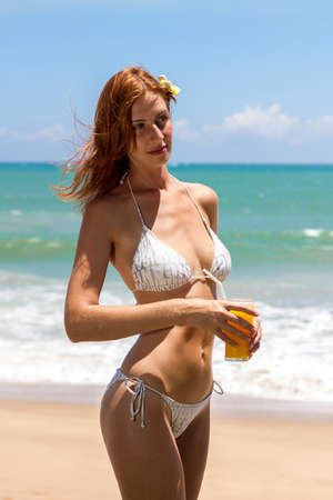 Young woman in bikini with cocktail on the beach photo