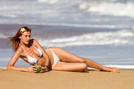 swimsuite: Young woman in bikini with cocktail lying on the beach Stock Photo