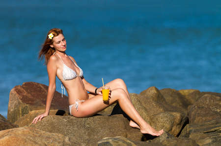 swimsuite: Young woman in bikini with cocktail sitting on the rocks Stock Photo