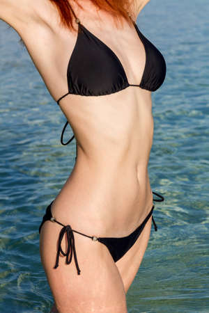 Close-up van slanke vrouw lichaam in zwarte bikini op het strand Stockfoto