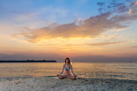Woman in yoga lotus meditation position back to seaside at sunset Stock Photo - 15869386