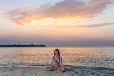 Woman in yoga lotus meditation position back to seaside at sunset photo