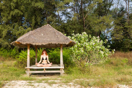 Young woman doing yoga lotus meditation in pavilion near ocean Stock Photo - 15869415