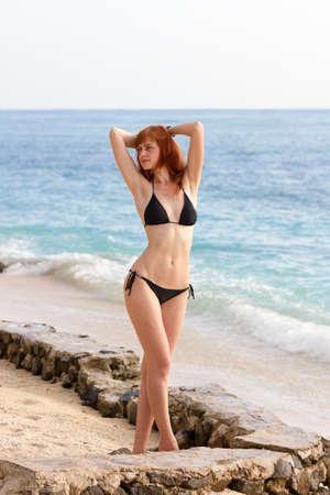 Young woman in bikini posing on sea coast standing
