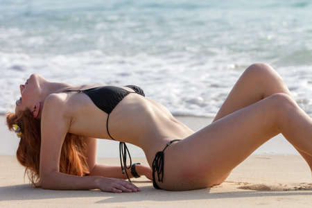 Young woman in bikini posing on sea coast lying
