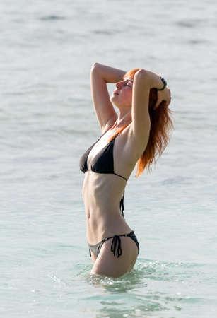 Young woman in bikini posing in ocean water standing