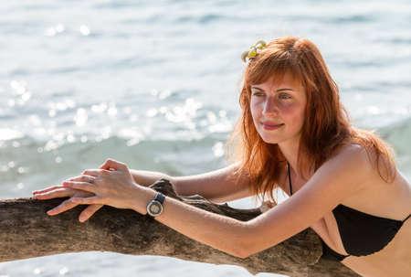 branchy: Young woman in bikini posing on branchy log in water Stock Photo
