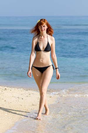 Young woman in bikini walking along sea coast Standard-Bild