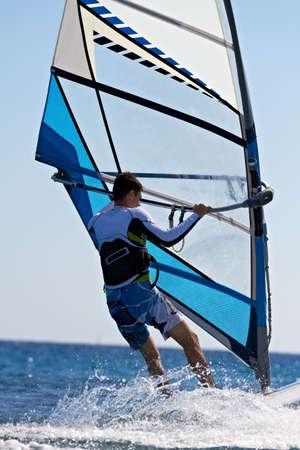 Achteraanzicht van de mens windsurfen in waterspatten close-up